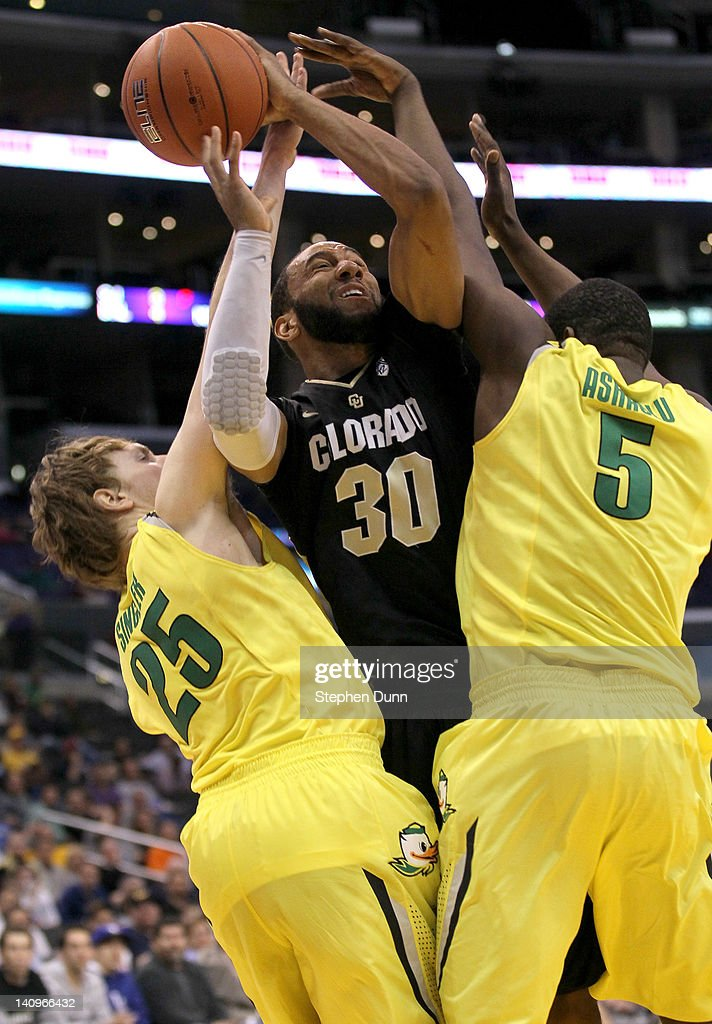 Carlon Brown #30 of the Colorado Buffaloes goes up for a shot between E.J. Singler #25 and Olu Ashaolu #5 of the Oregon Ducks during the quarterfinals of the Pac12 Men's Basketball Tournament at Staples Center on March 8, 2012 in Los Angeles, California. Colorado won 63-62.