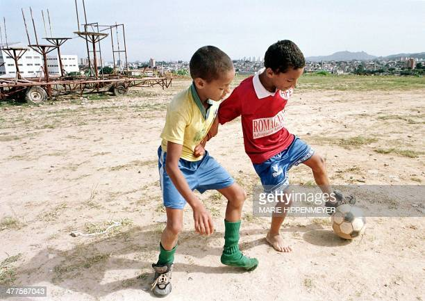 Carlos Alberto Ferreira wears the uniform of the Brazilian national soccer team while playing with his friend Paulo da Silva in a vacant lot in Sao...