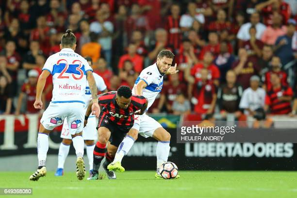 Carlos Alberto from Brazil's Atletico Paranaense struggles for the ball with Enzo Kalinski and German Lanaro from Chile's Universidad de Chile during...