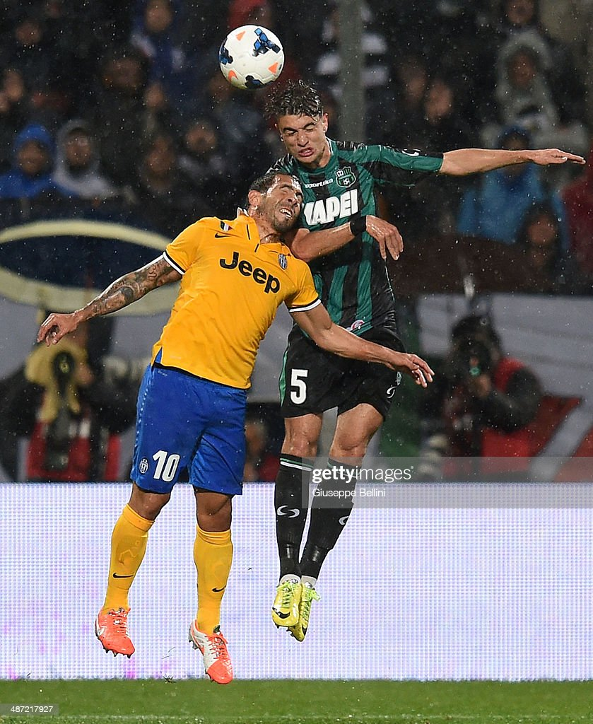 Carlos Alberto Tevez of Juventus and Luca Antei of Sassuolo in action during the Serie A match between US Sassuolo Calcio and Juventus at Mapei Stadium on April 28, 2014 in Sassuolo, Italy.