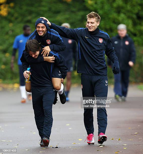 Carlos Alberto Vela jumps on the back of team mate Tomas Rosicky as Nicklas Bendtner laughs during a training session ahead of the UEFA Champions...