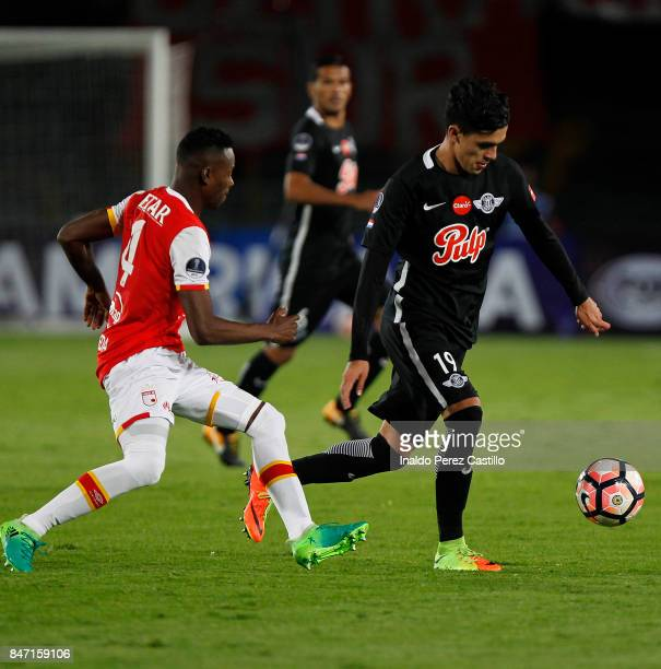 Carlos Arboleda of Santa Fe and Jose Medina of Libertad compete for the ball during a second leg match between Independiente Santa Fe and Libertad as...