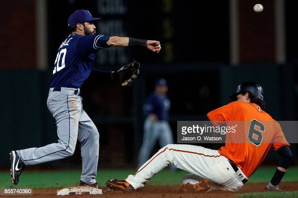 Carlos Asuaje of the San Diego Padres completes a double play over Jarrett Parker of the San Francisco Giants during the fifth inning at ATT Park on...