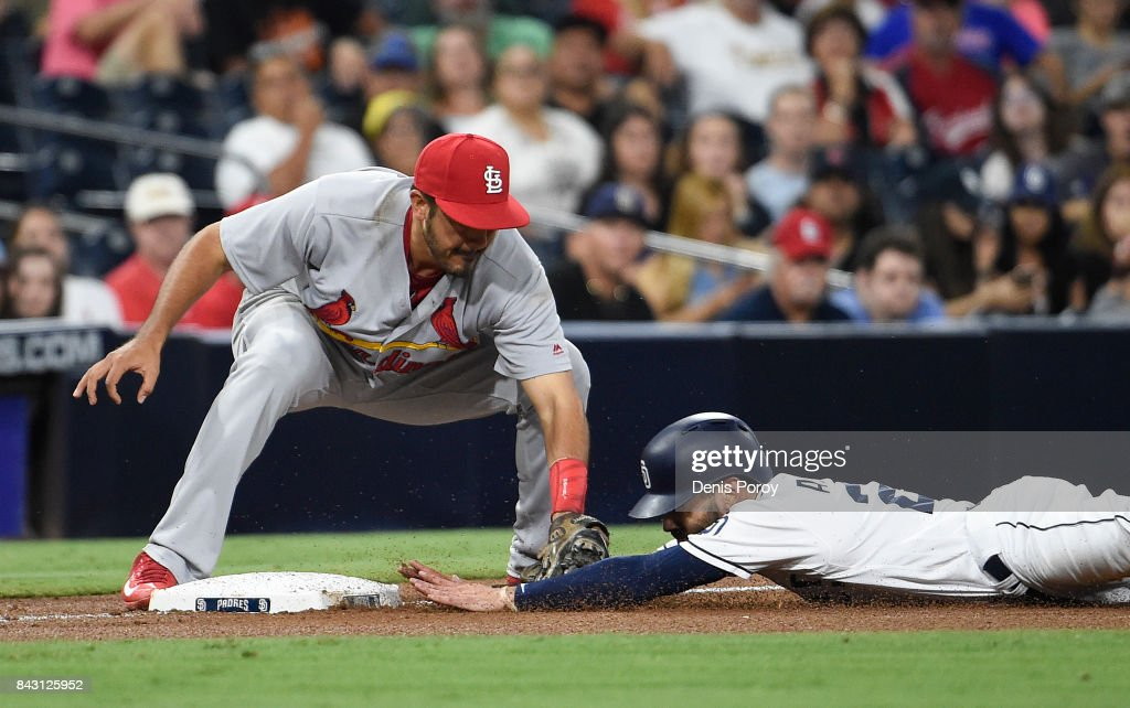 Carlos Asuaje #20 of the San Diego Padres is tagged out by Alex Mejia #54 of the St. Louis Cardinals as he slides into third base during the fifth inning of a baseball game at PETCO Park on September 5, 2017 in San Diego, California.