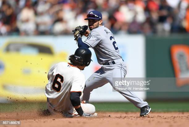 Carlos Asuaje of the San Diego Padres throws to first base over the top of Jarrett Parker of the San Francisco Giants but not in time to complete the...