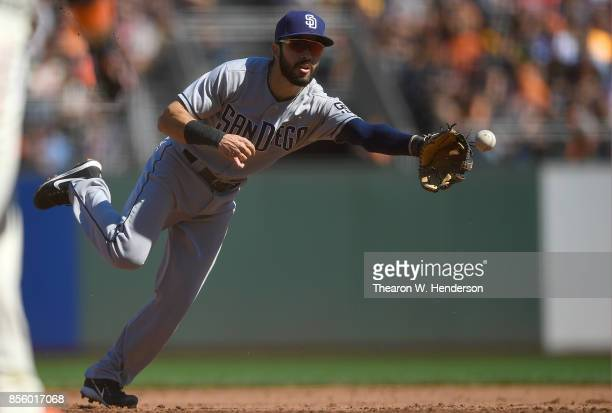 Carlos Asuaje of the San Diego Padres throws to the ball to first base using his glove to throw out Brandon Crawford of the San Francisco Giants in...