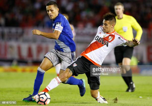 Carlos Auzqui of River Plate fights for the ball with Marcos Mondaini of Emelec during a group stage match between River Plate and Emelec as part of...