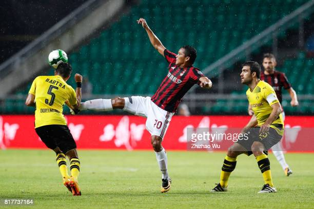 Carlos Bacca of AC Milan and Marc Bartra of Borussia Dortmund kick the ball at University Town Sports Centre Stadium on July 18 2017 in Guangzhou...