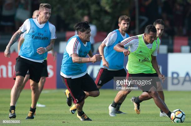 Carlos Bacca of AC Milan competes for the ball with his teammate Gustavo Gomez during the AC Milan training session at the club's training ground...