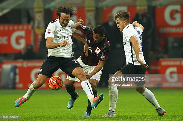 Carlos Bacca of AC Milan competes for the ball with Rafael Toloi and Cristin Raimondi of Atalanta BC during the Serie A match between AC Milan and...