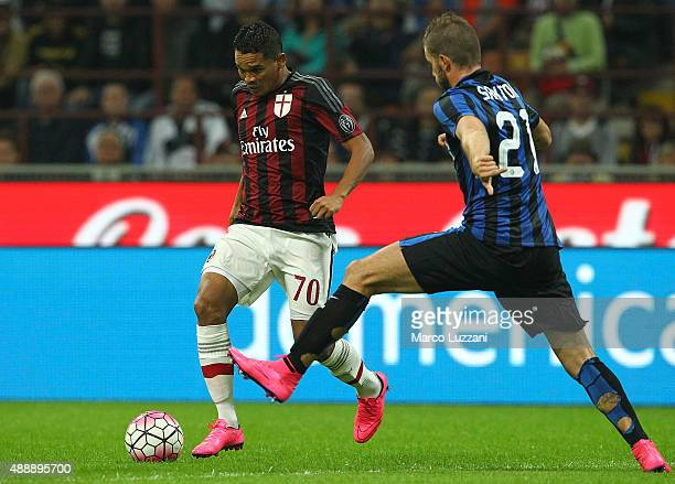 Carlos Bacca of AC Milan is challenged by Davide Santon of FC Internazionale Milano during the Serie A match between FC Internazionale Milano and AC...