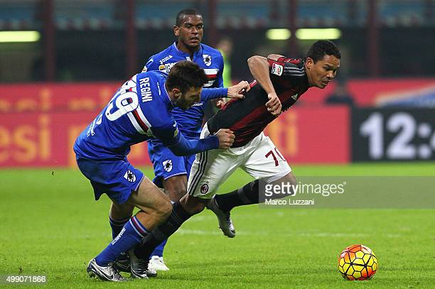 Carlos Bacca of AC Milan is challenged by Vasco Regini of UC Sampdoria during the Serie A match between AC Milan and UC Sampdoria at Stadio Giuseppe...