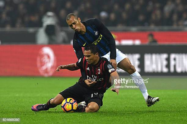 Carlos Bacca of AC Milan is tackled by Joao Miranda of FC Internazionale during the Serie A match between AC Milan and FC Internazionale at Stadio...