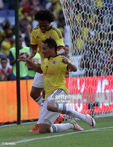 Carlos Bacca of Colombia celebrates with teammate Juan Cuadrado after scoring the opening goal during a match between Colombia and Ecuador as part of...