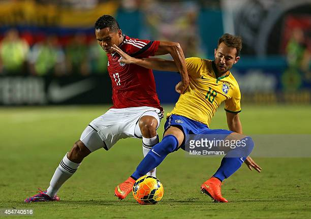 Carlos Bacca of Colombia is defended by Everton Ribeiro of Brazil during an International Soccer friendly at Sun Life Stadium on September 5 2014 in...