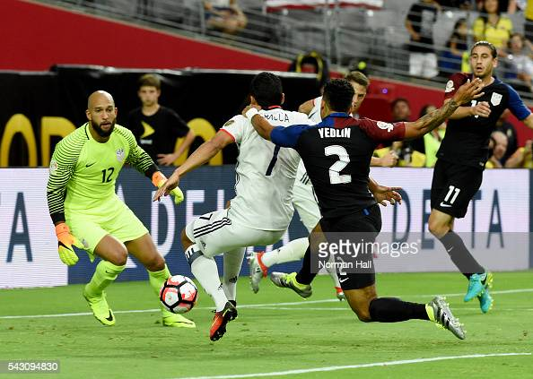 Carlos Bacca of Colombia takes a shot while being grabbed by DeAndre Yedlin of the United States in front of US goalkeeper Tim Howard during a third...