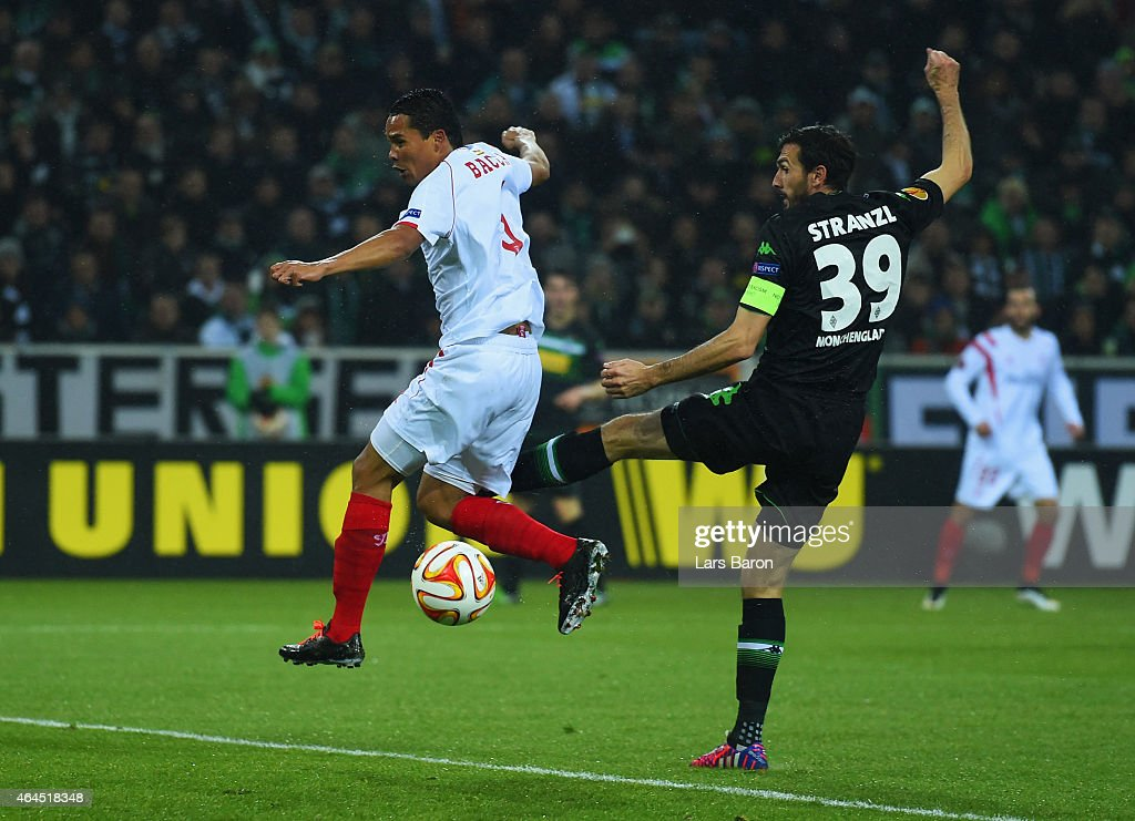 Carlos Bacca of Sevilla beats Martin Stranzl of Borussia Moenchengladbach to score their first goal during the UEFA Europa League Round of 32 second...