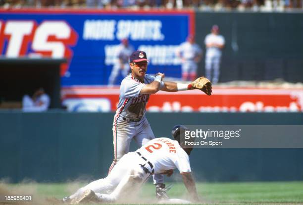 Carlos Baerga of the Cleveland Indians gets his throw off to first base while avoiding the slide of Mark McLemore of the Baltimore Orioles during an...