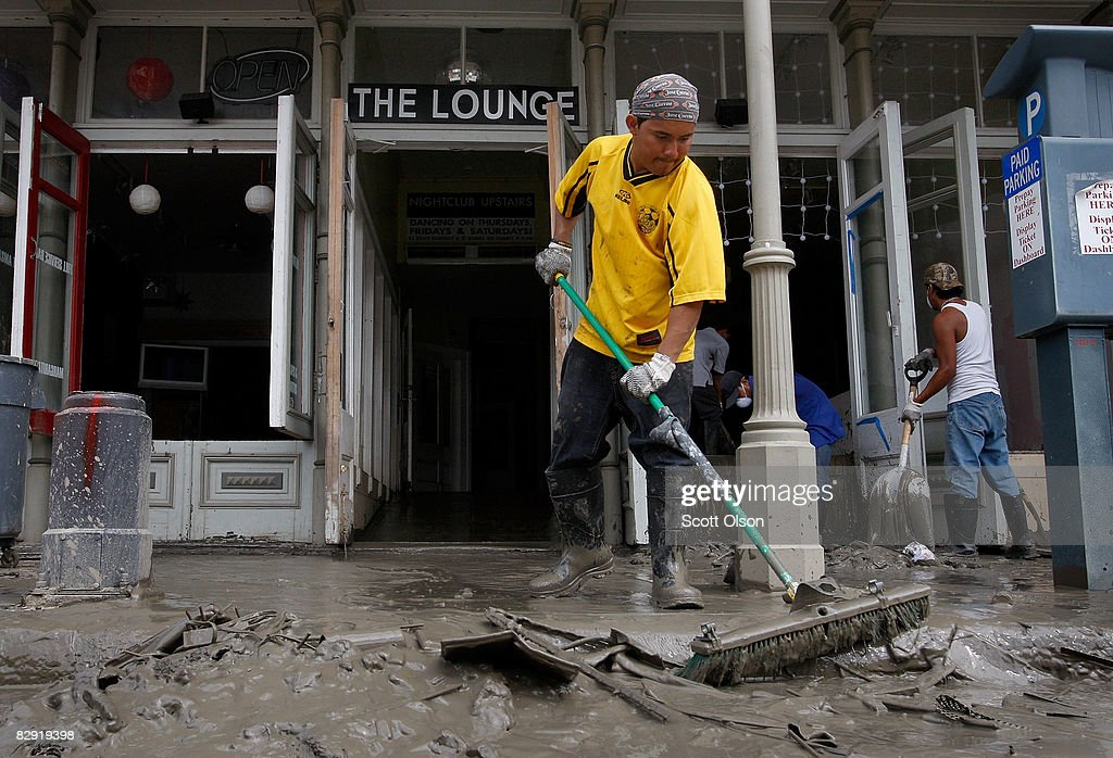 Carlos Barrilia pushes mud from The Lounge bar in the Strand District after it was flood damaged by Hurricane Ike September 19 2008 in Galveston...