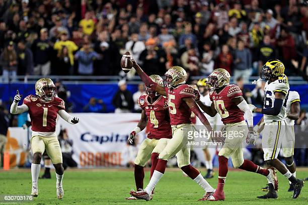 Carlos Becker III of the Florida State Seminoles and teammates celebrate in the final seconds of their 33 to 32 win over the Michigan Wolverines...