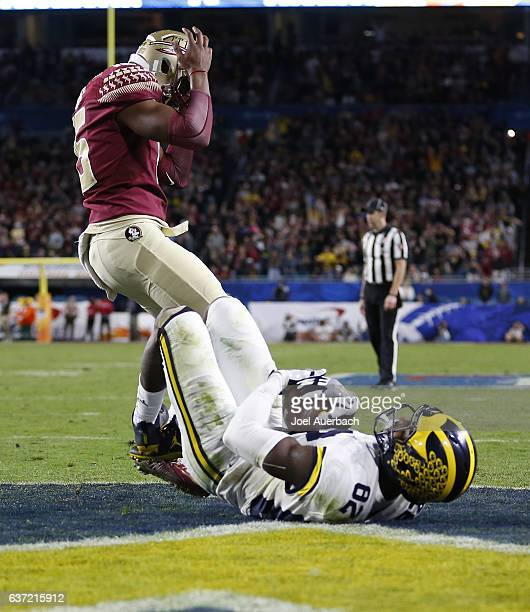 Carlos Becker III of the Florida State Seminoles holds his head as Amara Darboh of the Michigan Wolverines catches the ball to complete a two point...