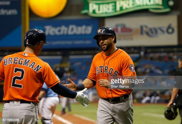 Carlos Beltran of the Houston Astros celebrates with Alex Bregman after scoring off of an RBI single by Brian McCann during the 10th inning of a game...