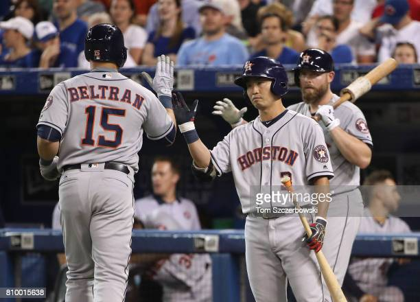Carlos Beltran of the Houston Astros is congratulated by Norichika Aoki after hitting a solo home run in the eighth inning during MLB game action...