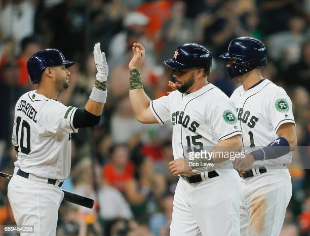 Carlos Beltran of the Houston Astros receives high fives from Yuli Gurriel after scoring in the second inning against the Baltimore Orioles at Minute...