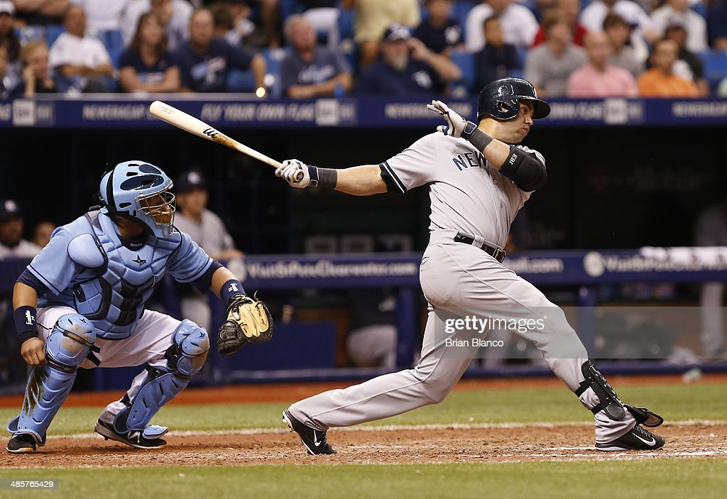 Carlos Beltran #36 of the New York Yankees hits a two-run single in front of Jose Molina #28 of the Tampa Bay Rays to score Brian McCann and Jacoby Ellsbury during the top of the 12th inning of a game on April 20, 2014 at Tropicana Field in St. Petersburg, Florida.