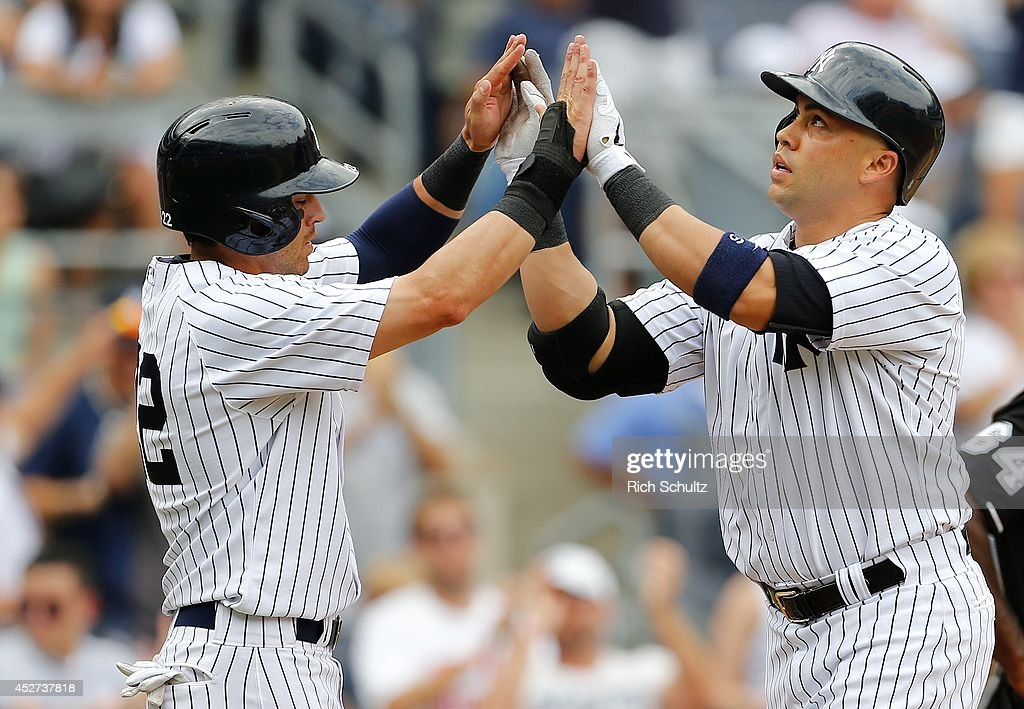 Carlos Beltran of the New York Yankees is congratulated by teammate Jacoby Ellsbury after hitting a tworun home run in the ninth inning during an MLB...