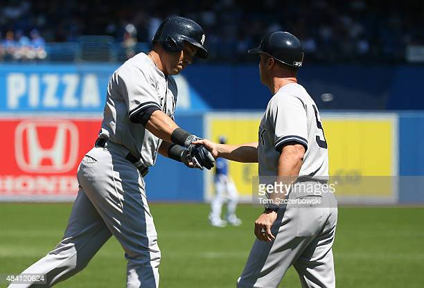 Carlos Beltran of the New York Yankees is congratulated by third base coach Joe Espada ##54 after hitting a solo home run in the first inning during...
