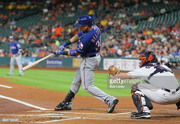 Carlos Beltran of the Texas Rangers doubles in the first inning as Evan Gattis of the Houston Astros looks on at Minute Maid Park on September 14...