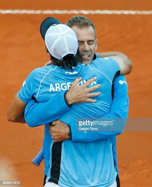Carlos Berlocq of Argentina hugs to Daniel Orsanic captain of Argentina to celebrate after wining the singles match between Carlos Berlocq and Paolo...