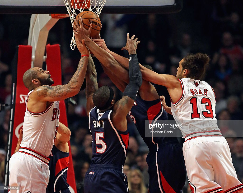 Carlos Boozer #5 (L) and Joakim Noah #13 of the Chicago Bulls battle for a rebound with Josh Smith #5 and Al Horford #15 of the Atlanta Hawks at the United Center on January 14, 2013 in Chicago, Illinois.