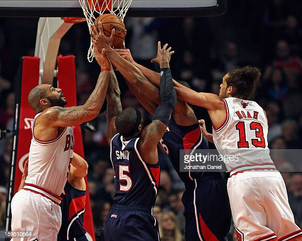 Carlos Boozer and Joakim Noah of the Chicago Bulls battle for a rebound with Josh Smith and Al Horford of the Atlanta Hawks at the United Center on...