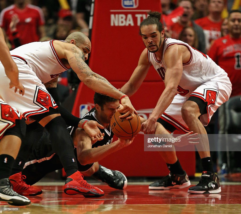 Carlos Boozer and Joakim Noah of the Chicago Bulls strip the ball from Brook Lopez of the Brooklyn Nets in Game Six of the Eastern Conference...