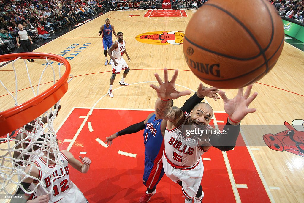 Carlos Boozer #5 of the Chicago Bulls battles for a rebound with Andre Drummond #1 of the Detroit Pistons on March 31, 2013 at the United Center in Chicago, Illinois.