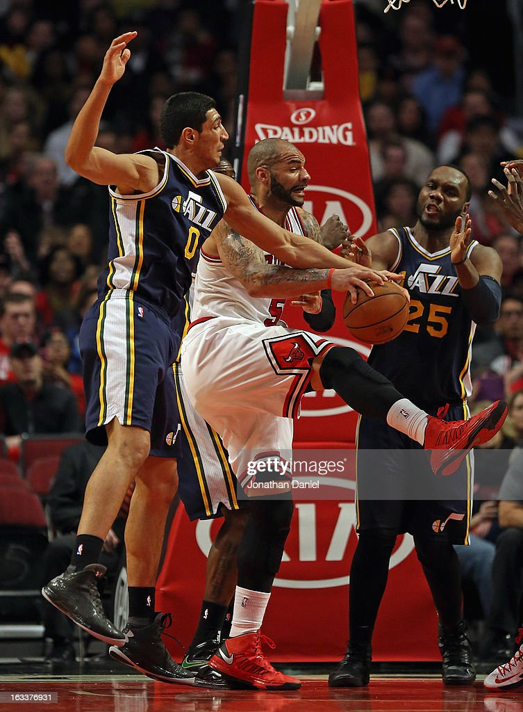 Carlos Boozer #5 of the Chicago Bulls battles for a rebound with Enes Kanter #0 and Al Jefferson #25 of the Utah Jazz at the United Center on March 8, 2013 in Chicago, Illinois.