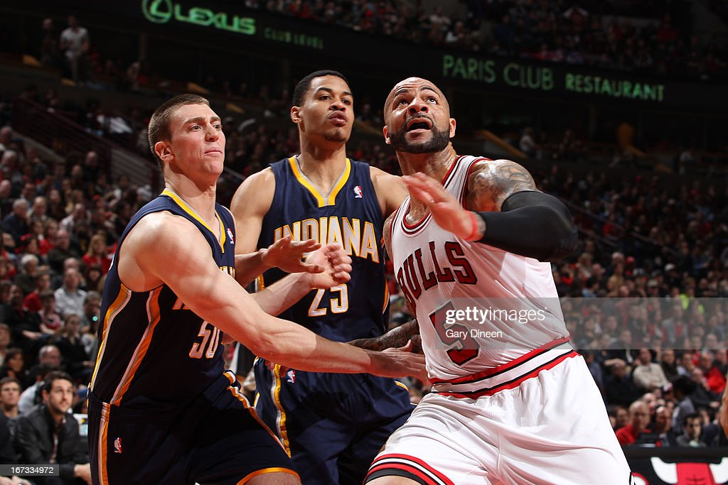 Carlos Boozer #5 of the Chicago Bulls boxes out Tyler Hansbrough #50 and Gerald Green #25 of the Indiana Pacers on March 23, 2013 at the United Center in Chicago, Illinois.