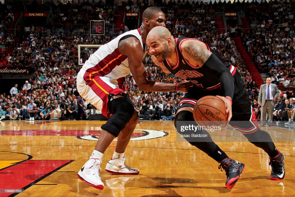 <a gi-track='captionPersonalityLinkClicked' href=/galleries/search?phrase=Carlos+Boozer&family=editorial&specificpeople=201638 ng-click='$event.stopPropagation()'>Carlos Boozer</a> #5 of the Chicago Bulls drives against <a gi-track='captionPersonalityLinkClicked' href=/galleries/search?phrase=Chris+Bosh&family=editorial&specificpeople=201574 ng-click='$event.stopPropagation()'>Chris Bosh</a> #1 of the Miami Heat on January 4, 2013 at American Airlines Arena in Miami, Florida.