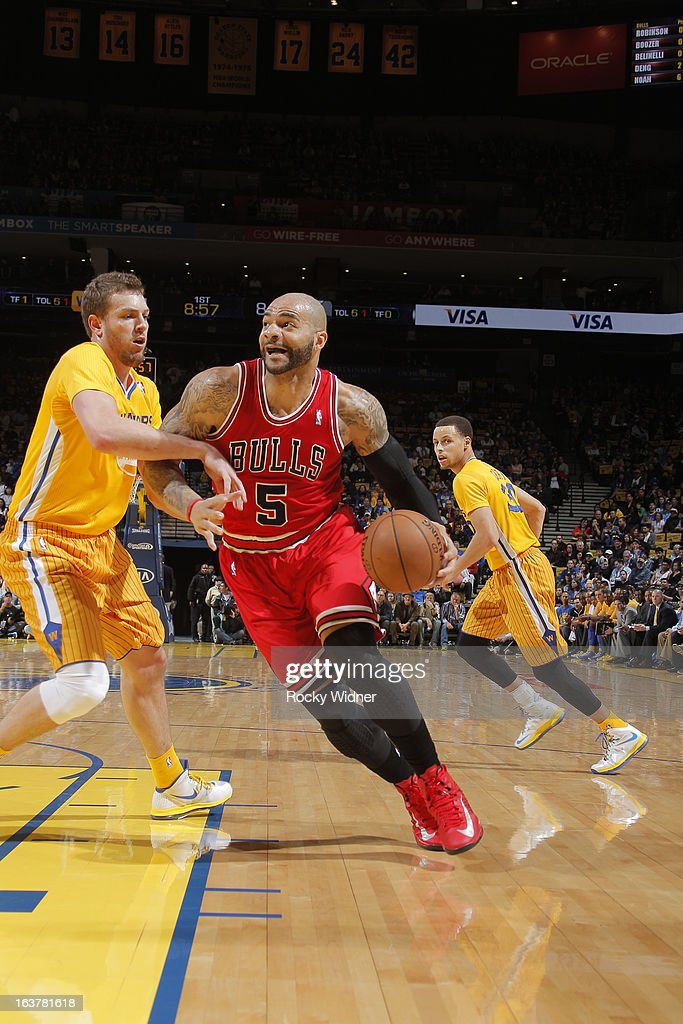 Carlos Boozer #5 of the Chicago Bulls drives to the basket against David Lee #10 of the Golden State Warriors on March 15, 2013 at Oracle Arena in Oakland, California.