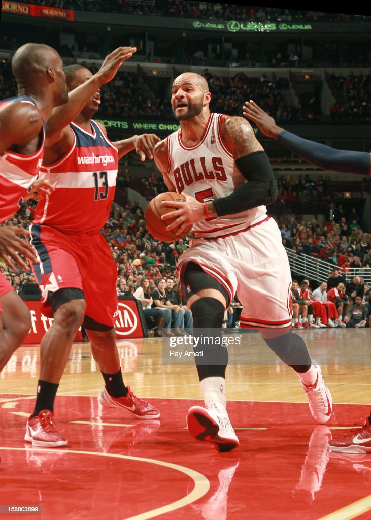 Carlos Boozer #5 of the Chicago Bulls drives to the basket against Kevin Seraphin #13 and Emeka Okafor #50 of the Washington Wizards on December 29, 2012 at the United Center in Chicago, Illinois.