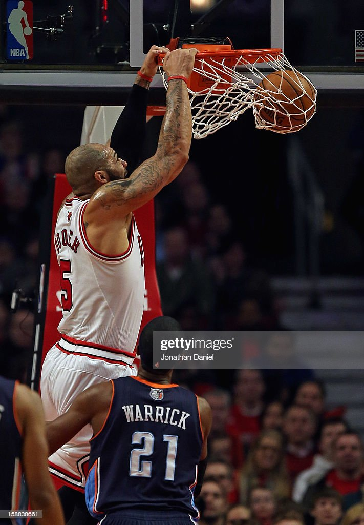Carlos Boozer #5 of the Chicago Bulls dunks over Hakim Warrick #21 of the Charlotte Bobcats at the United Center on December 31, 2012 in Chicago, Illinois.