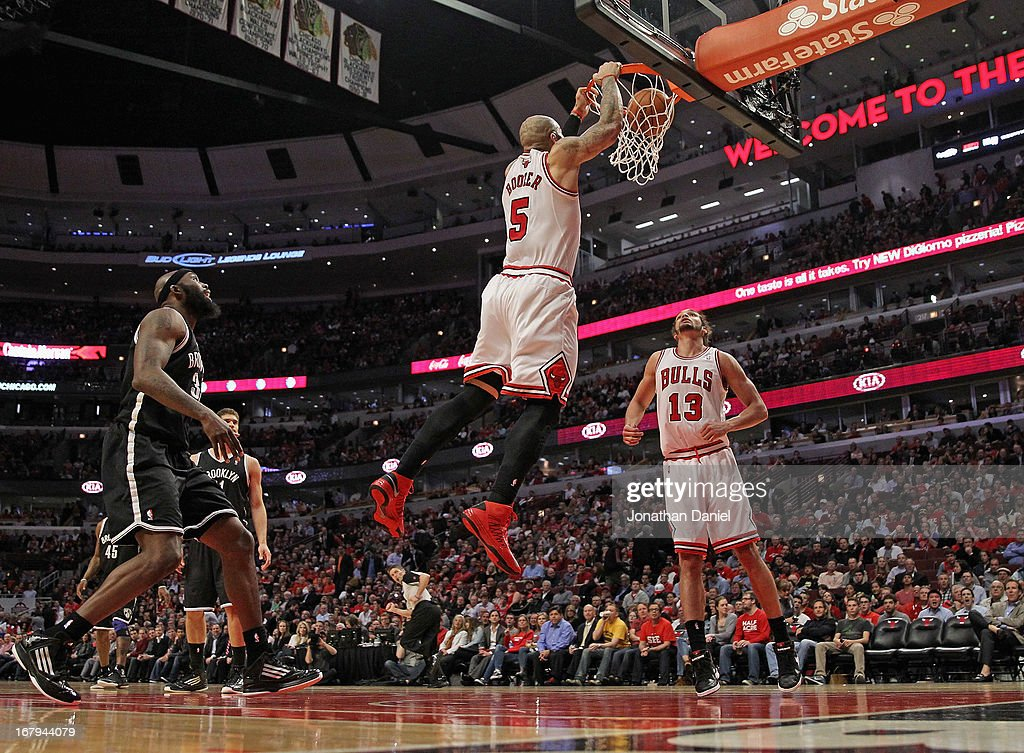 Carlos Boozer #5 of the Chicago Bulls goes up for a dunk over teammate Joakim Noah #13 and past Reggie Evans #30 of the Brooklyn Nets in Game Six of the Eastern Conference Quarterfinals during the 2013 NBA Playoffs at the United Center on May 2, 2013 in Chicago, Illinois. The Nets defeated the Bulls 95-92.