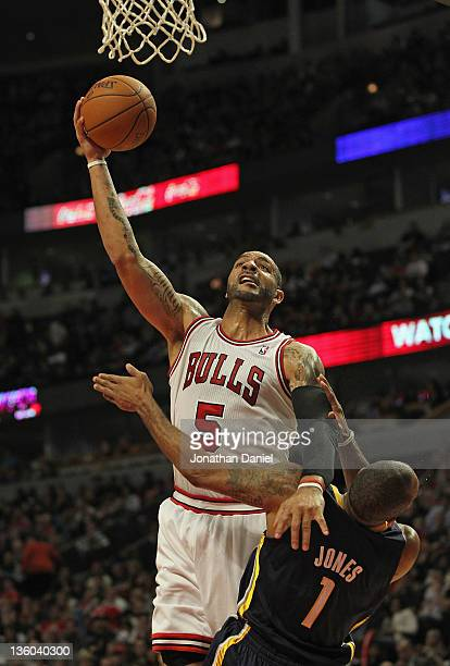 Carlos Boozer of the Chicago Bulls goes up for a shot over Dahntay Jones of the Indiana Pacers at the United Center on December 20 2011 in Chicago...