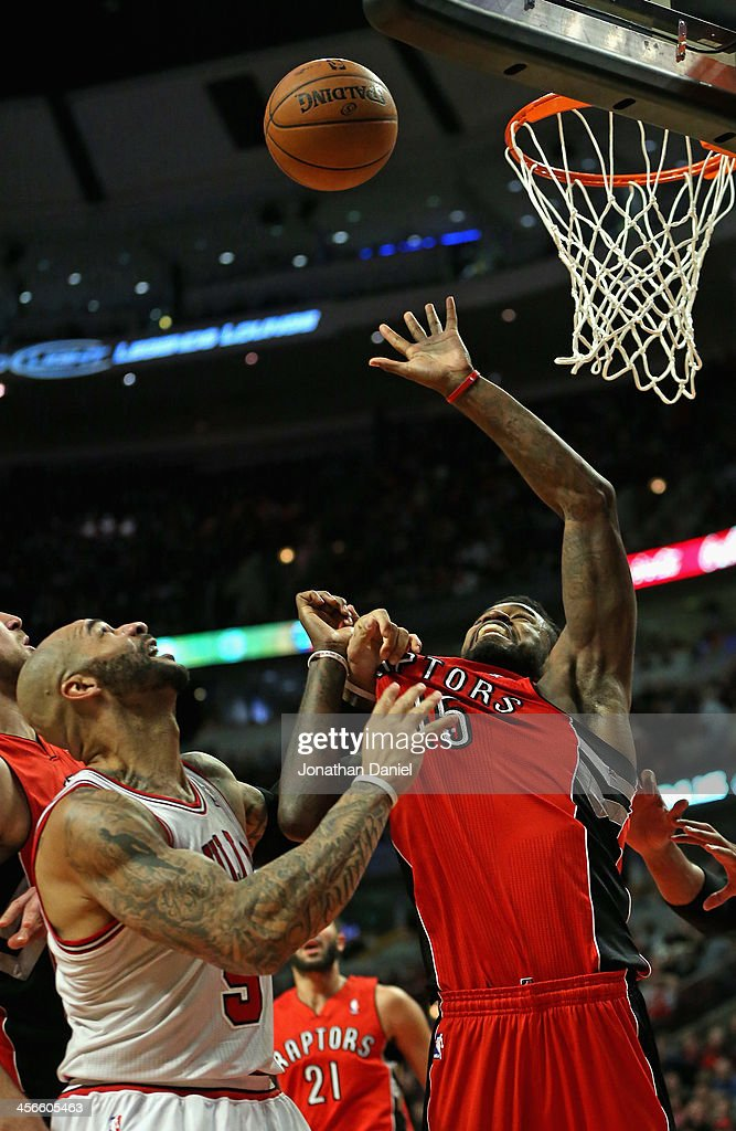 <a gi-track='captionPersonalityLinkClicked' href=/galleries/search?phrase=Carlos+Boozer&family=editorial&specificpeople=201638 ng-click='$event.stopPropagation()'>Carlos Boozer</a> #5 of the Chicago Bulls grabs the jersey <a gi-track='captionPersonalityLinkClicked' href=/galleries/search?phrase=Amir+Johnson&family=editorial&specificpeople=556786 ng-click='$event.stopPropagation()'>Amir Johnson</a> #15 of the Toronto Raptors as he tries for a rebound at the United Center on December 14, 2013 in Chicago, Illinois. The Raptors defeated the Bulls 99-77.