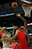 Carlos Boozer of the Chicago Bulls grabs the jersey Amir Johnson of the Toronto Raptors as he tries for a rebound at the United Center on December 14...