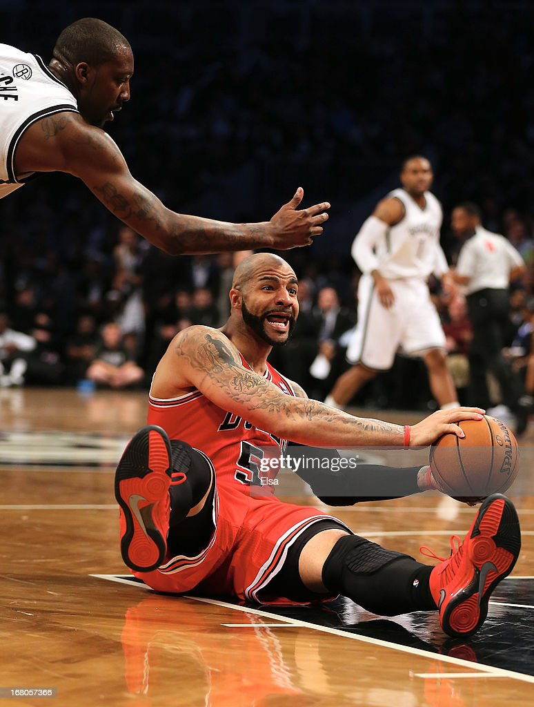 Carlos Boozer #5 of the Chicago Bulls grabs the loose ball as Andray Blatche #0 of the Brooklyn Nets defends during Game Seven of the Eastern Conference Quarterfinals of the 2013 NBA Playoffs on May 4, 2013 at the Barclays Center in the Brooklyn borough of New York City. The Chicago Bulls defeated the Brooklyn Nets 99-93.