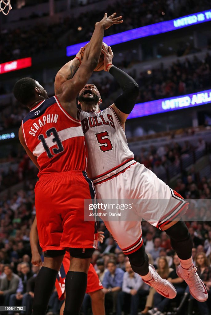 Carlos Boozer #5 of the Chicago Bulls is fouled by Kevin Seraphin #13 of the Washington Wizards at the United Center on April 17, 2013 in Chicago, Illinois. The Bulls defeated the Wizards 95-92.