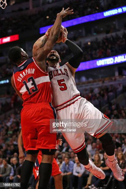Carlos Boozer of the Chicago Bulls is fouled by Kevin Seraphin of the Washington Wizards at the United Center on April 17 2013 in Chicago Illinois...